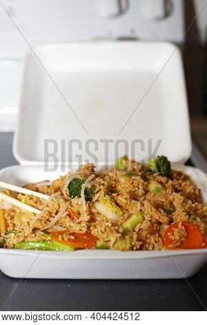 Thai Noodles And Rice With Tofu, Broccoli And Carrots In A Carryout Container