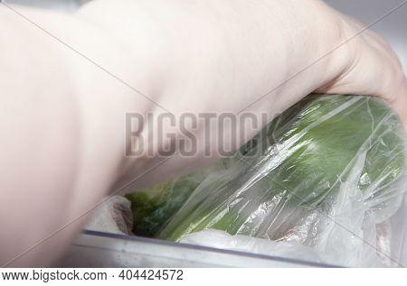 Woman Grabbing Green Bell Peppers From A Refridgerator
