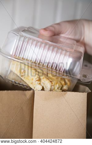 Woman Pulling A Fresh Pastry Box Out Of A Grocery Bag