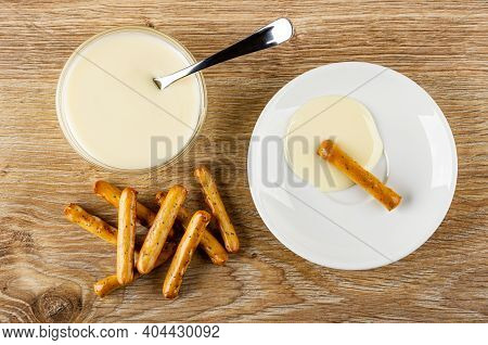 Teaspoon, Condensed Milk In Glass Bowl, Breadsticks With Poppy On Table, Breadstick With Condensed M