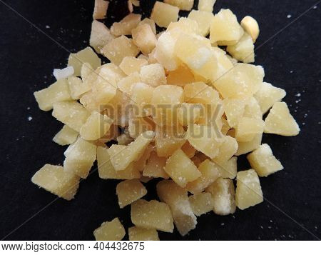 Closeup Of Yellow Color Jaggery Slices Or Cut Pieces In A Sand Bowl And Plastic Cup Isolated On Blac