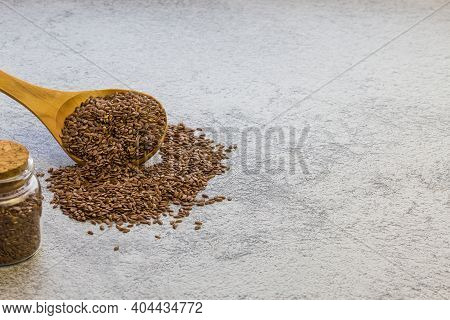 Flax Seeds In A Wooden Spoon And A Glass Jar On Concrete Background, A Dietary Product That Reduces