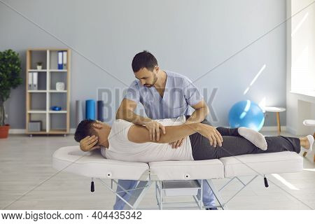 Chiropractor, Osteopath, Physiotherapist Or Manual Therapist Helping Patient With Backache