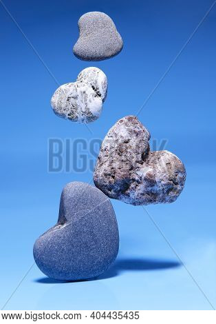 Levitation. Falling Stones In The Shape Of A Heart On A Blue Background. Stone Hearts Of Different S