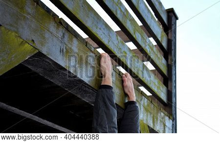 Young Man Hangs On A Wooden Railing And Tries To Step Up, His Hand Slides And He Clings To The Rescu