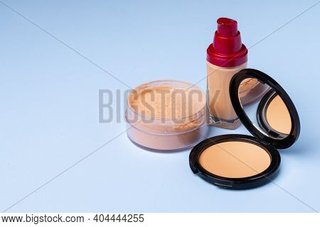 Complexion Make Up Products And Brush On Blue Background