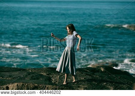Dancer is engaged in choreography on the rocky coast of Atlantic ocean.