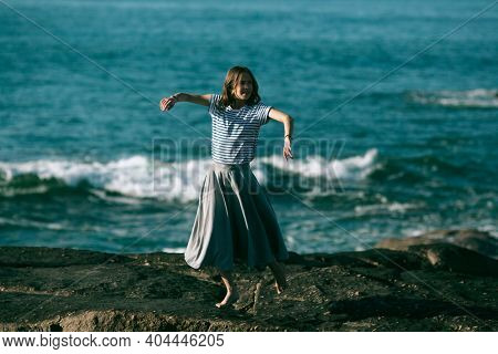 Dancer woman is engaged in choreography on the rocky coast of Atlantic ocean.