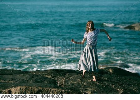 Dancer girl is engaged in choreography on the rocky coast of Atlantic ocean.