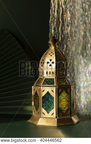Beautiful Traditional Moroccan Lantern On A Dark Emerald Background With Paper Fan And Tinsel Bokeh