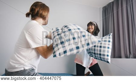 Pillow Fight. Happy Young Multiracial Couple Fighting With Pillows In The Bedroom. High Quality Phot