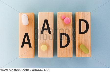 Aadd Abbreviation On Cubes With Pill On A Blue Background. Close Aadd - Adult Attention Deficit Diso