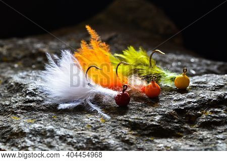 Group Of Colorful Jig Streamer Made Of Feathers On Gray Stone