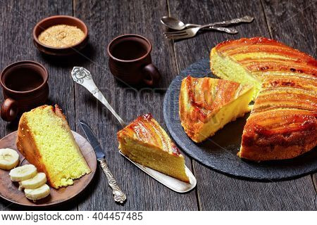 Upside-down Banana Cake Cut In Slices On A Black Round Stone Plate On A Rustic Wooden Table, Horizon