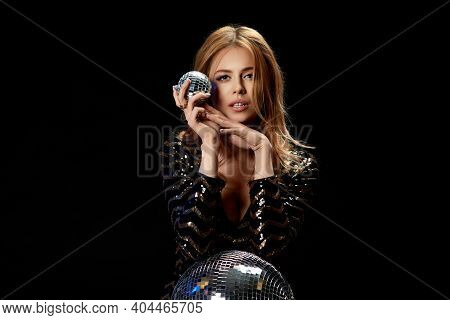 Sexy Model Posing On Near Disco Ball. Gorgeous Curly Blonde Woman In A Black Sequins Dress For Party