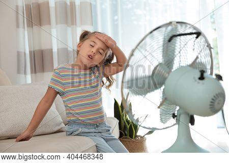 Little Girl Enjoying Air Flow From Fan On Sofa In Living Room. Summer Heat