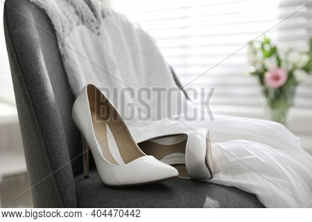 Pair Of White High Heel Shoes And Wedding Dress On Chair Indoors