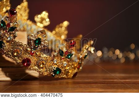 Beautiful Golden Crown And Fairy Lights On Wooden Table, Closeup. Fantasy Item