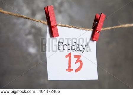 Paper Note With Phrase Friday! 13 Hanging On Twine Against Grey Background. Bad Luck Superstition