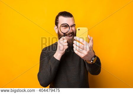 Photo Of Bearded Man Looking Trough Magnifying Glass At Smartphone