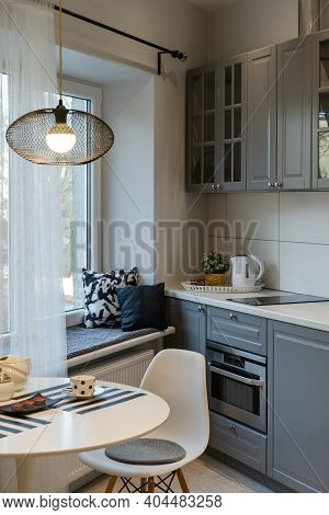 Interior Of The Newly Equipped Kitchen Part In The Studio Apartment. Round Table With Lamp, Chair By