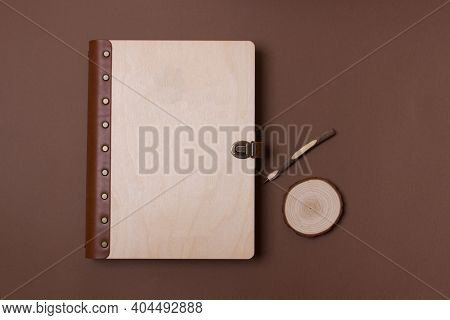 Family Photo Book. Photo Book On Brown Background With Wooden Pen. Brown Photo Book With Wood Cover.