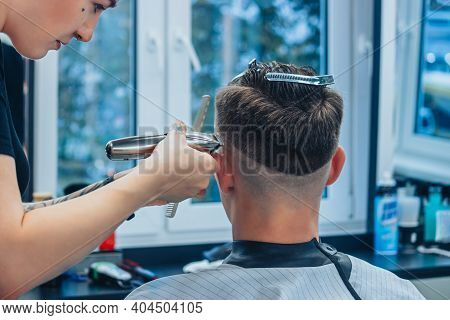 Minsk, Belarus - October 14, 2020: A Tattooed Woman Hairdresser At A Barbershop Cuts A Young Guy's H