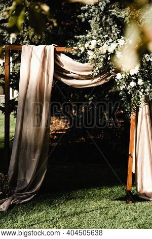 A Brown Silk Fabric Hangs From A Wooden Wedding Altar Decorated With Roses. Wedding Decorations. Flo