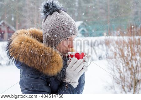 Middle Age Woman Holding A Cup Of Hot Drink At Background Of A Winter Street. Outdoor Shoot.a Girl I