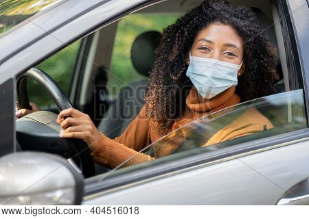 African Woman With Curly Hair With Face Mask On Sitting And Driving Car. Prevention From Spreading C