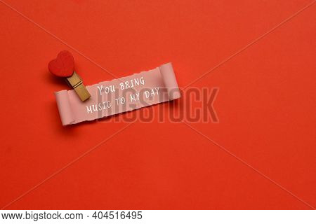You Bring Music To My Day Label On Torn Paper With Red Paper Background. Valentine's Day Concept