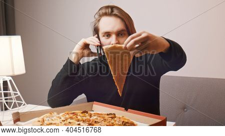 Young Caucasian Man Complaining About Pizza On The Phone. Holding One Slice While Using Smartphone.
