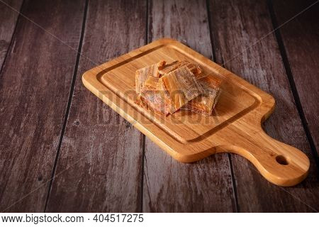 Dried Fish Fillet On A Cutting Board With Wooden Dark Background. Thai Food Concept.