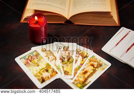 Milan,italy-january 19,2021: Tarot Cards With Candlelight And Book On The Darkness Background,hallow