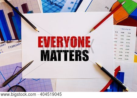 The Word Everyone Matters Is Written On A White Background Near Colored Graphs, Pens And Pencils. Bu