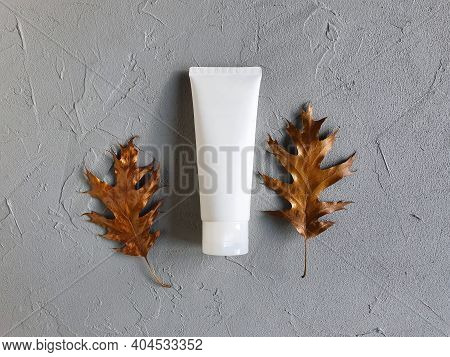 Mockup Of White Squeeze Bottle Plastic Tube And Golden Leaves Frame On Gray Textured Background. Tre