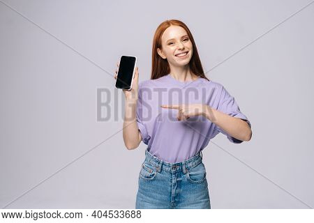 Portrait Of Cheerful Young Woman In Stylish Casual Clothes Pointing With Finger On Blank Mobile Scre