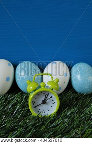 Easter Holiday. Blue And White Easter Eggs And Green Alarm Clock In Green Grass On A Bright Blue Tur