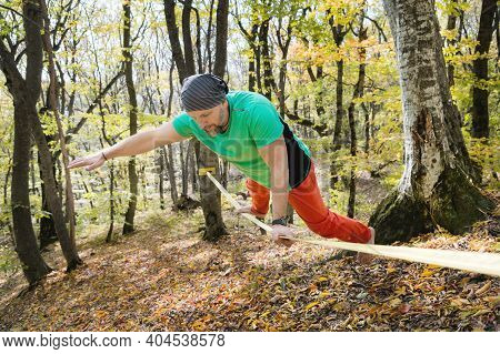 A Bearded Man In Age Balances While Sitting On A Taut Slackline In The Autumn Forest. Outdoor Leisur