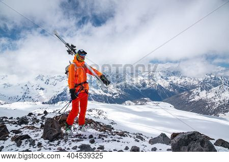 Young Sportsman Skier In Mask With Skis On The Background Of The Caucasus Mountains