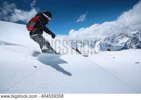 Young Woman Snowboarder In Deep Snow - Extreme Freeride On The Background Of Snow-capped Mountains O