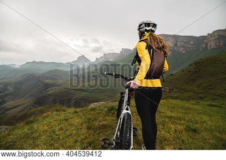 Wide Angle Bottom View Of A Young Woman Sitting On A Mountain Bike High In The Mountains Against The