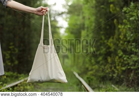 White Tote Bag Canvas Fabric With Handle Mock Up Design. Close Up Of Woman's Hand Holding Eco Or Reu