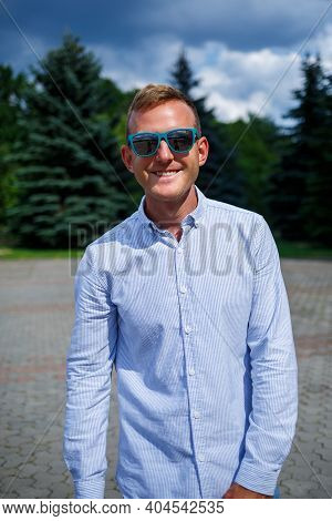 A Handsome Young Man Of European Appearance Wearing Sunglasses Is Dressed In A Shirt And Jeans. The