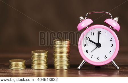 Gold Money Coin Stacks With Alarm Clock, Covid-19 Pandemic Financial Stimulus Aid Package Concept