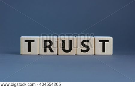 Trust Symbol. Concept Word 'trust' On Wooden Cubes On A Beautiful Grey Background. Business And Trus