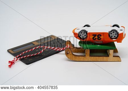 An Overturned Toy Car Lies On A Sled, Near A Calculator, A Symbol Of Auto Insurance And New Year's D