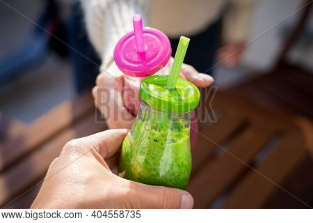 Couple Hands Clinking Bottles Of Tasty Pink And Green Homemade Detox Smoothie Or Juice. Healthy Deto