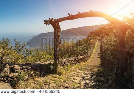 An Old Wooden Archway In Front Of The Beginning Of An Old Rural Trail. Aerial View Of Las Playas. Th