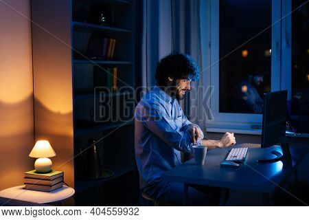 Side View Of Young Freelancer Working On Computer And Rolling Up His Shirt Sleeves While Sitting At